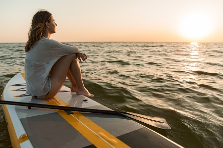 Beautiful young woman sitting on a stand up paddle board on a water